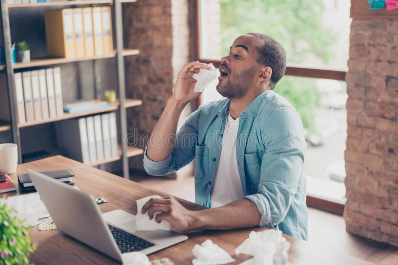 Young ill afro student is sneezing at work place in modern office, a lot of paper napkins on desktop and in his arm stock photo