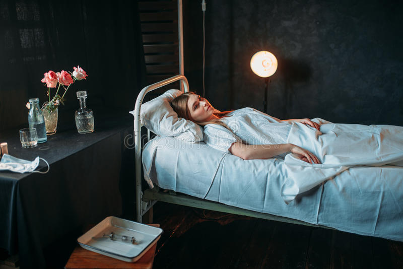 Young ill woman lying in hospital bed royalty free stock images