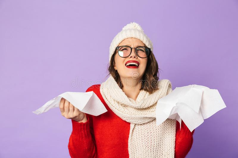 Young ill woman wearing winter hat isolated over purple background holding napkin. Portrait of a young ill woman wearing winter hat isolated over purple stock images