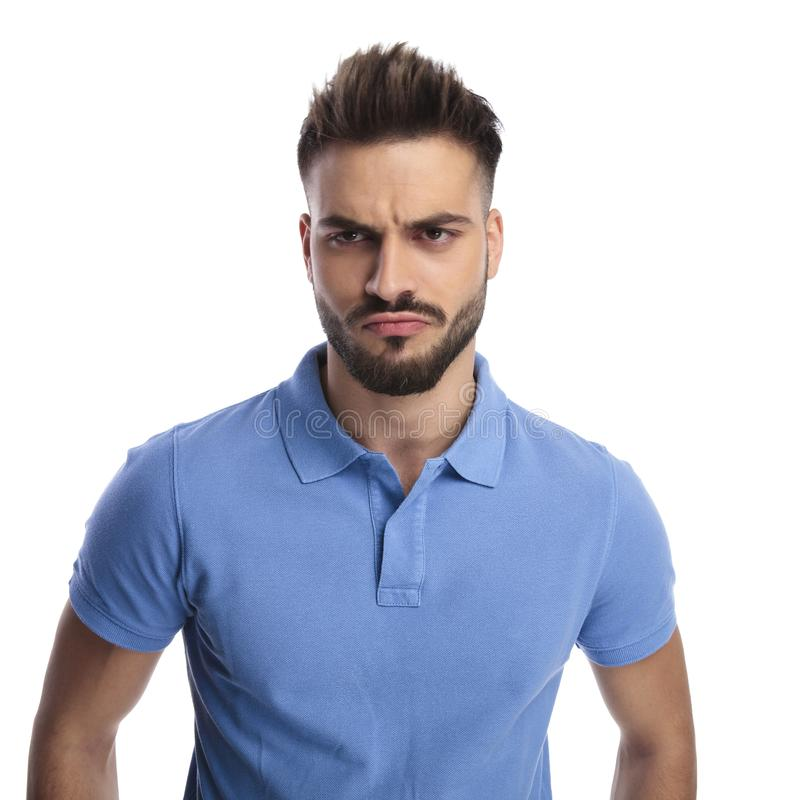 Young imature man wearing a light blue polo frowning. While looking at a side on a light background stock photo