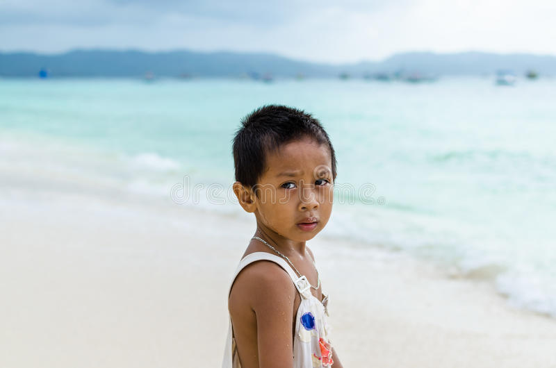 Young impoverished asian boy at white beach on Boracay royalty free stock images