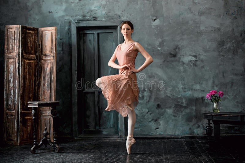 Young and incredibly beautiful ballerina is posing and dancing in a black studio stock photos