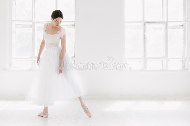 Young and incredibly beautiful ballerina is posing and dancing in a white studio stock images