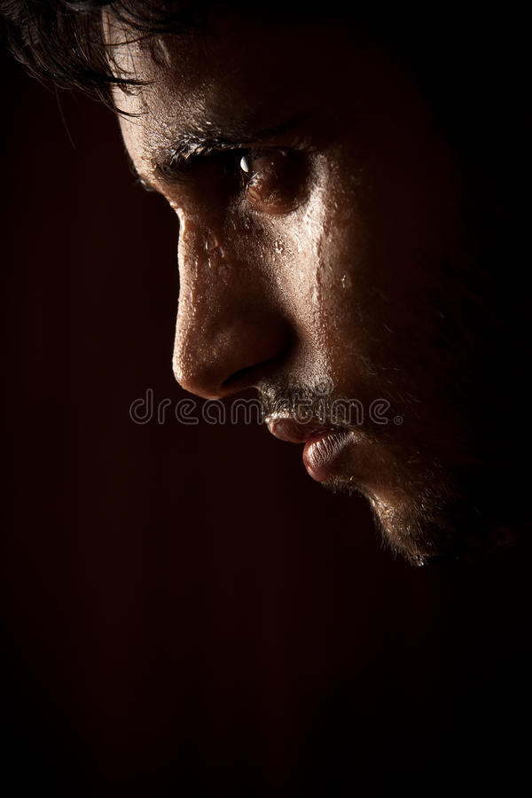 Young Indian angry man sweating over dark. Grains & textures are added in the portrait of Indian angry man sweating over dark background royalty free stock image