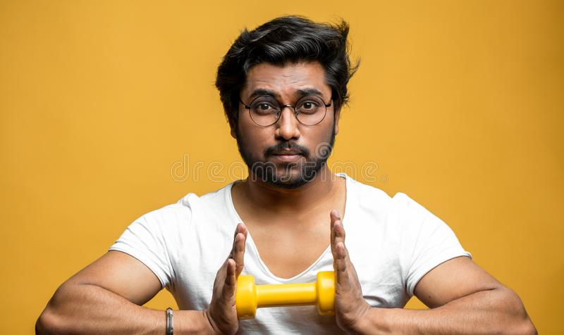 Young Indian athlete holding yellow dumbbell and doing exercises stock photos