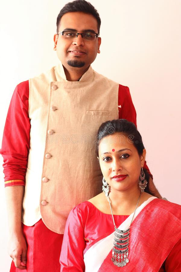 A young indian bengali assamese couple dressed in red and white ethnic indian dress and smiling stock photos