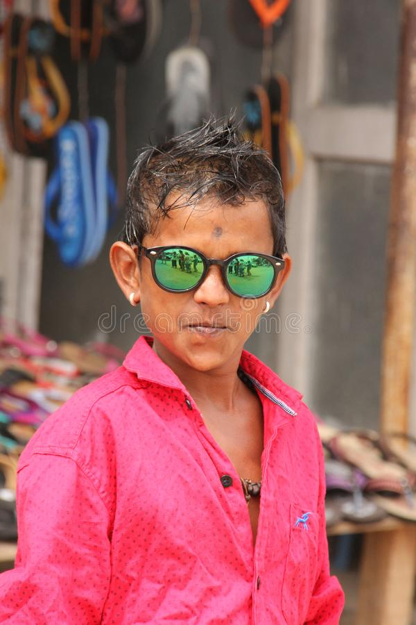 A right little poser. A young indian boy posing in his metallic sunglasses with tourists reflecting in them royalty free stock images