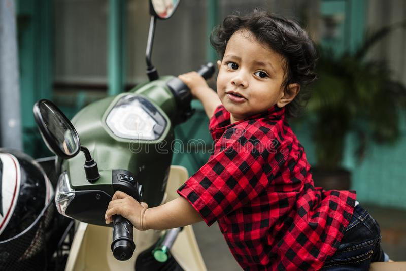 Young Indian boy riding the motorbike royalty free stock image