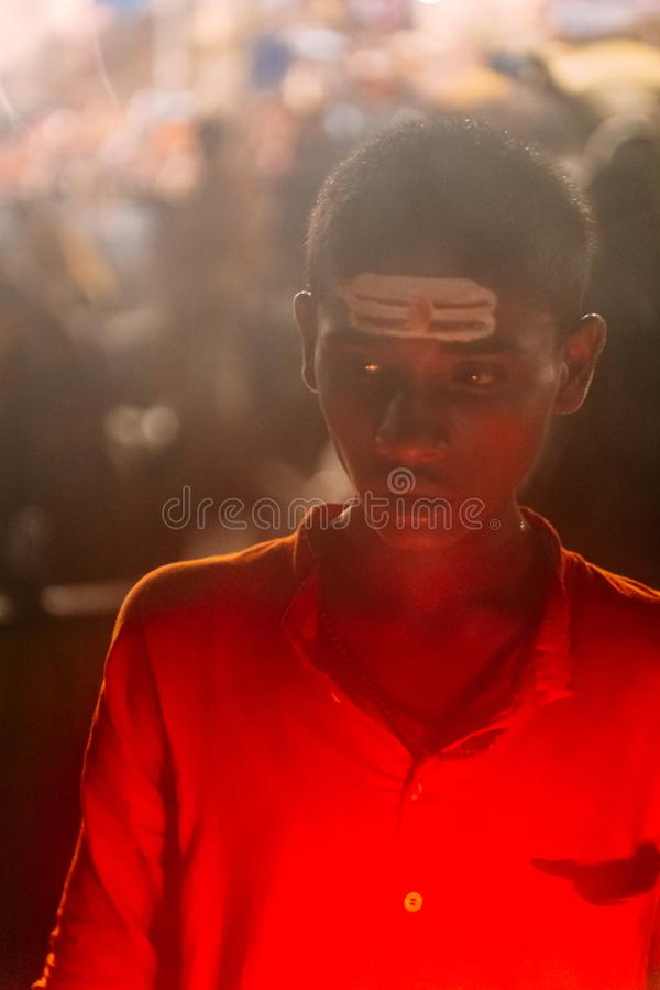 Young Indian boy wearing red on the boat in the area of Varanasi Ganga Aarti at holy Dasaswamedh Ghat. Young Indian boy wearing red on the boat in the area of royalty free stock images