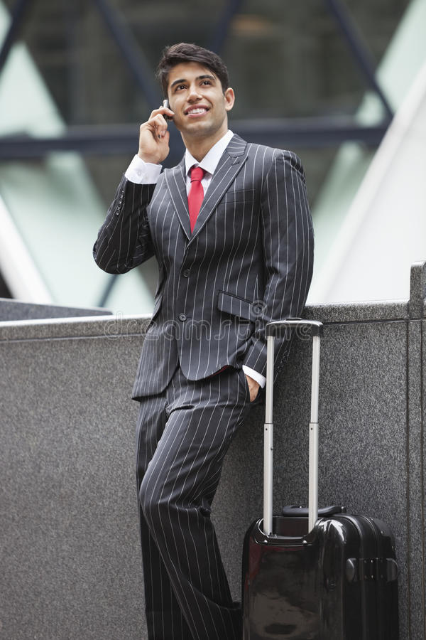 Young Indian businessman communicating on cell phone while standing next to luggage bag stock photos