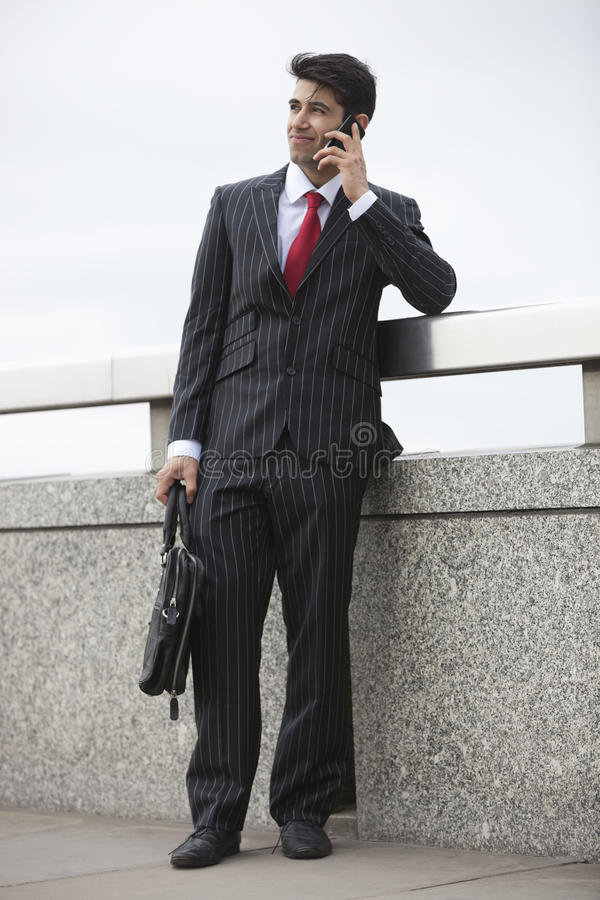 Download Young Indian Businessman Using Cell Phone With Laptop Bag By Parapet Stock Photo - Image: 30854210