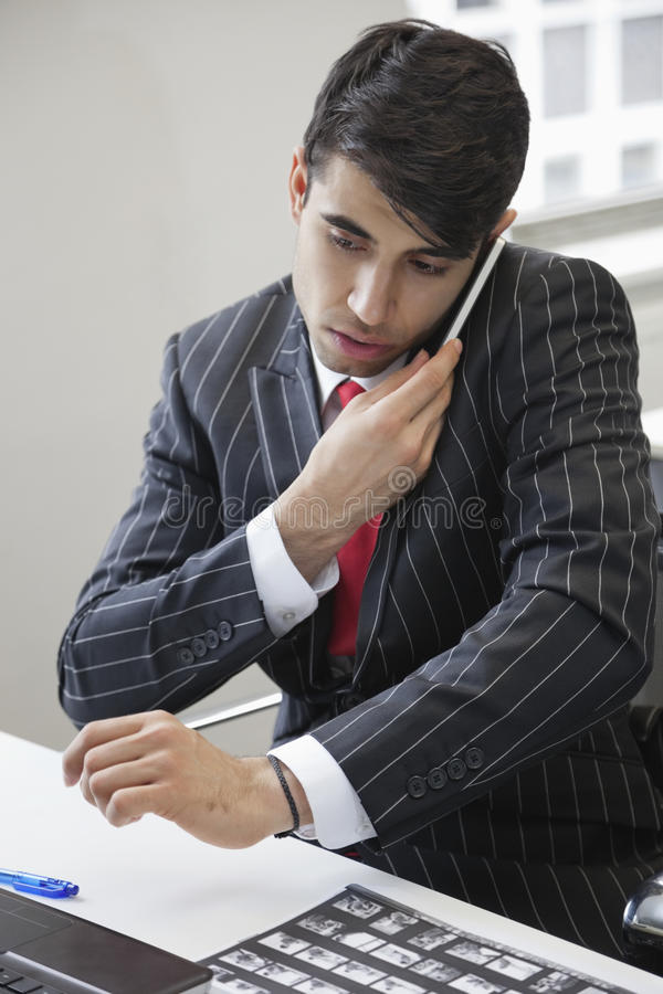 Young Indian businessman using cell phone at office desk royalty free stock photography