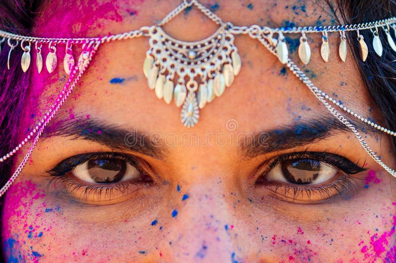 Young Indian face in paint Woman in traditional indian pink outfit with jeweler celebrating Holi color festival.girl. With black hair with bindi on the head royalty free stock image