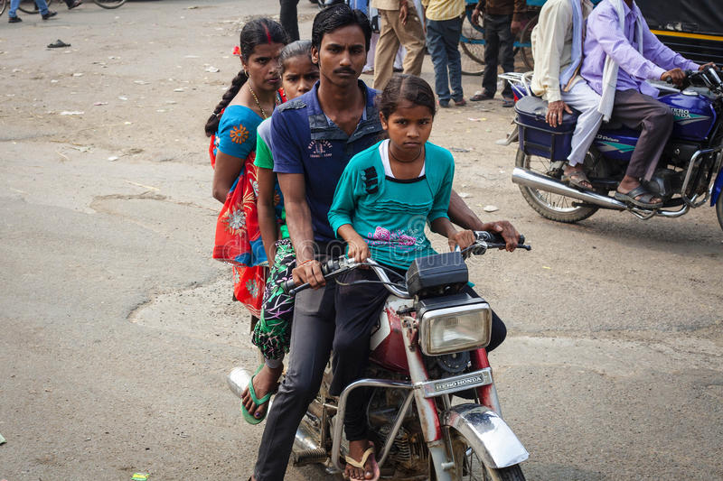 Young indian family with a lot children riding on rikshaw. VARANASI, INDIA - OCTOBER 28: Young indian family with a lot children riding on rikshaw. Motorbike is stock image