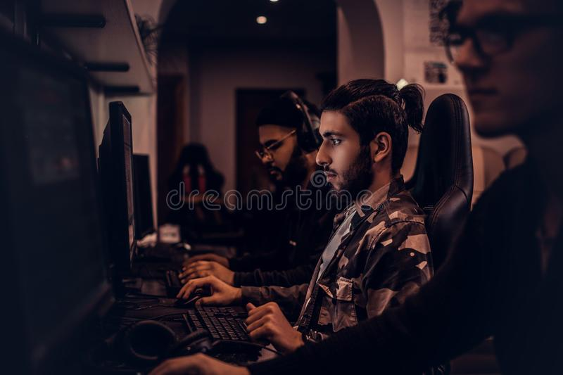 A young Indian gamer plays in a multiplayer video game on pc in a gaming club, enjoying spending time with her friends. stock images