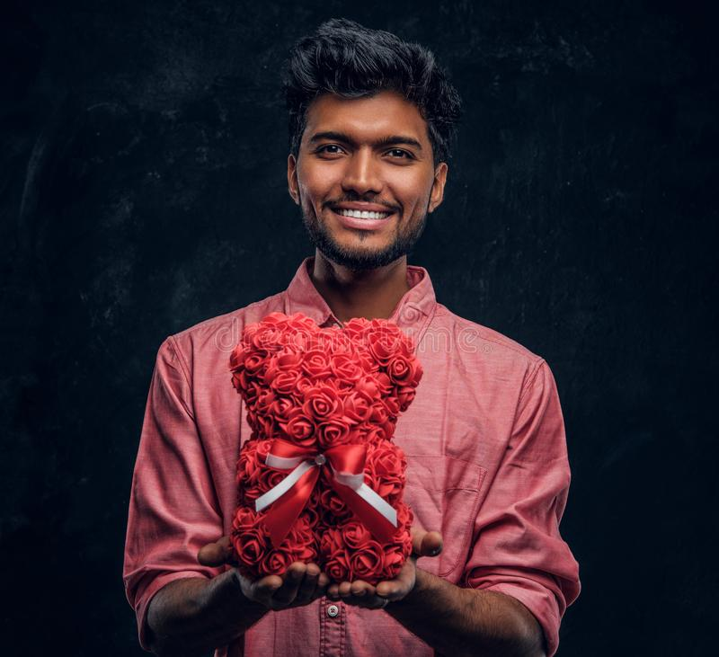 Indian guy in a pink shirt holds a beautiful gift, smiling and looking at the camera. Romantic mood, love relationship. A young Indian guy in a pink shirt holds stock photography