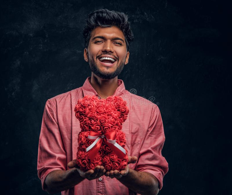 Indian guy in a pink shirt holds a beautiful gift, smiling and looking at the camera. Romantic mood, love relationship. A young Indian guy in a pink shirt holds stock images