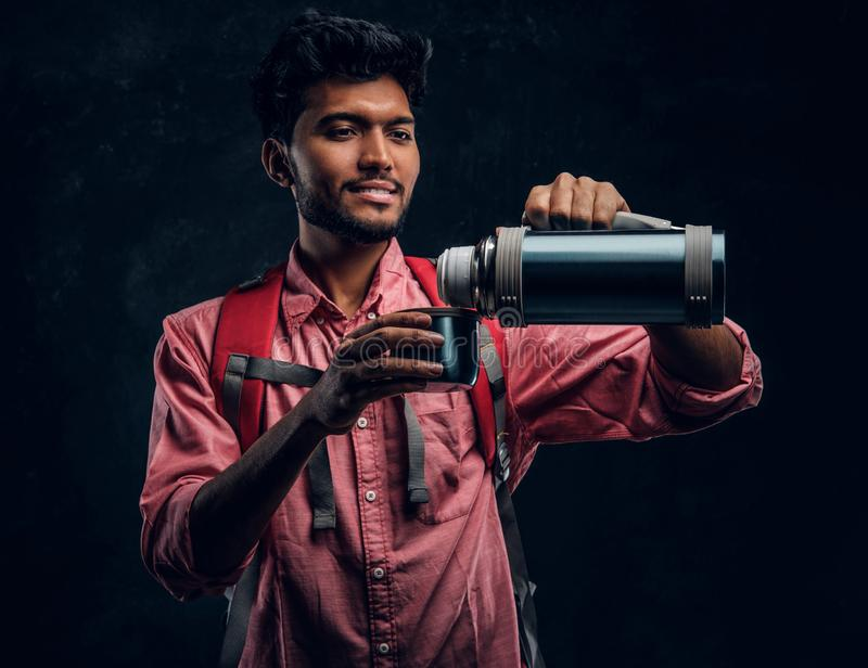 Young Indian hiker pours his own tea from a thermos. Studio photo against a dark textured wall royalty free stock image