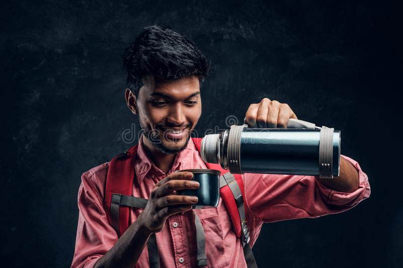 Young Indian hiker pours his own tea from a thermos. Studio photo against a dark textured wall stock photos