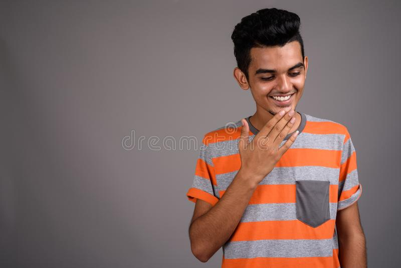Young Indian man against gray background stock images