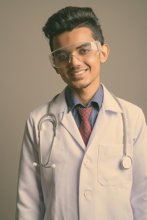 Young Indian man doctor wearing protective glasses against gray background royalty free stock photos