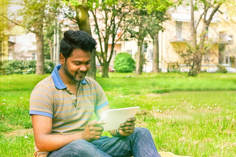 Young indian man having video call on tablet in park university camp - Concept of new technology miracle addiction - Soft warm royalty free stock image
