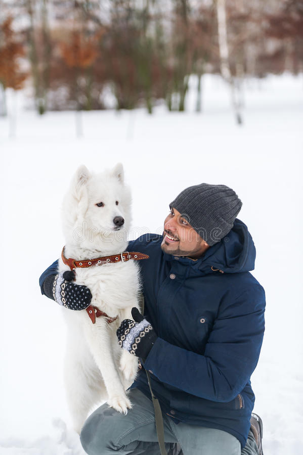 Young indian man and solid white fluffy dog in winter day. royalty free stock photos