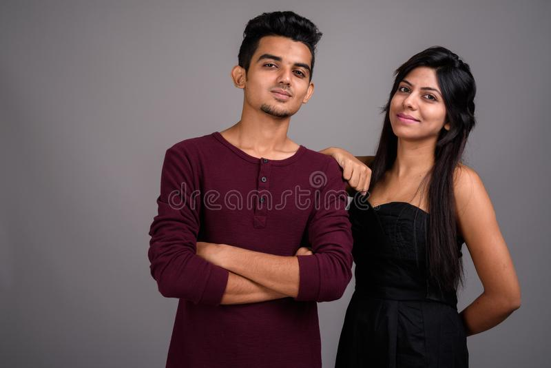 Young Indian man and young Indian woman together against gray ba royalty free stock photos