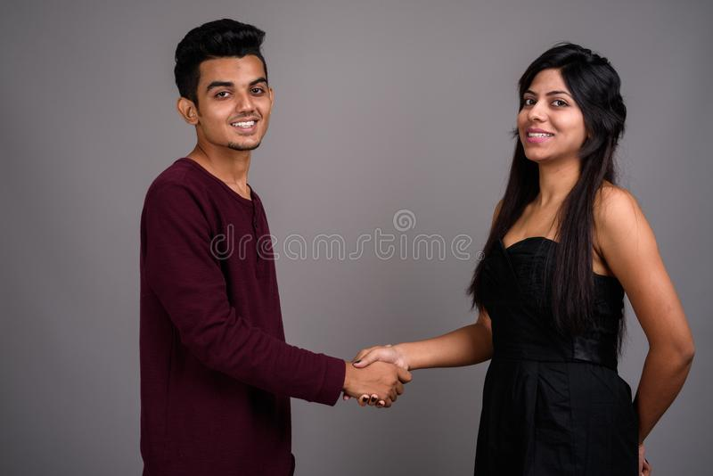 Young Indian man and young Indian woman together against gray ba stock images