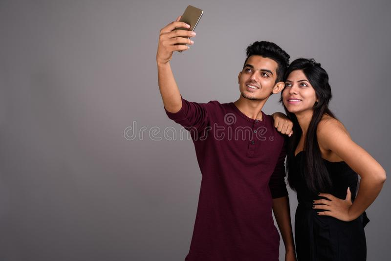 Young Indian man and young Indian woman together against gray ba stock photography