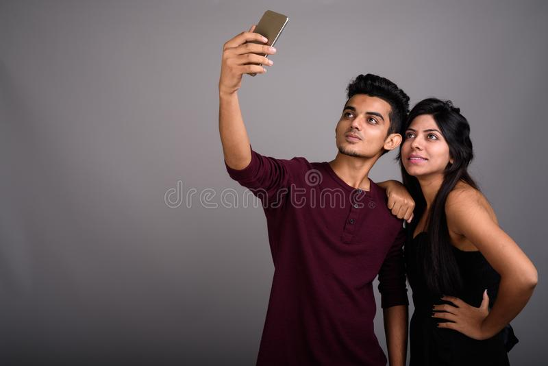 Young Indian man and young Indian woman together against gray ba stock photo