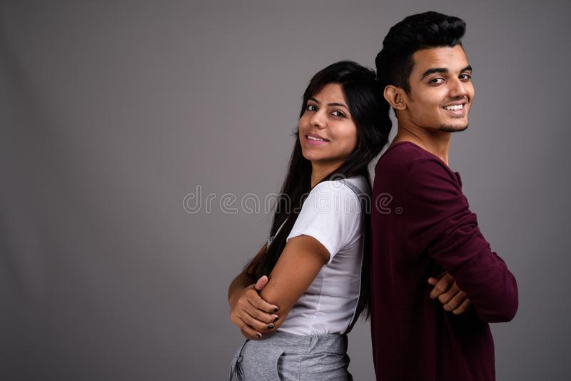 Young Indian man and young Indian woman together against gray ba royalty free stock photo