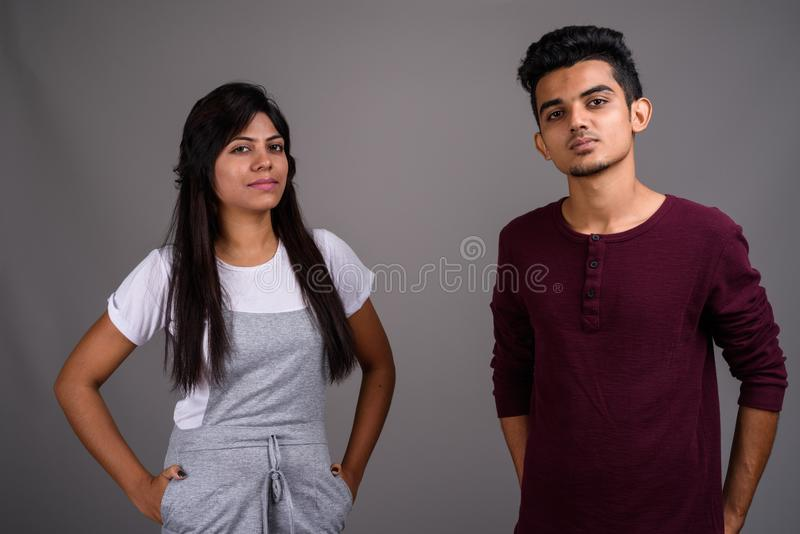 Young Indian man and young Indian woman together against gray ba royalty free stock image