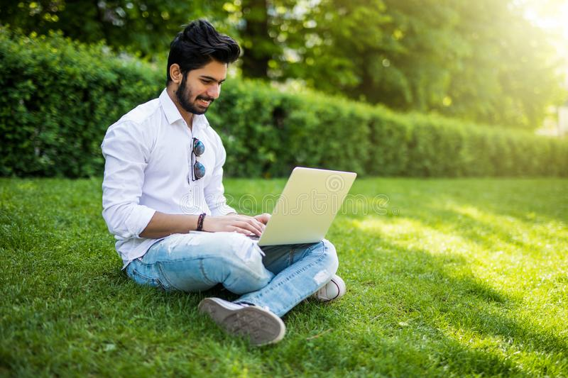 Young indian Student man with a laptop sitting on the grass. Urban style. stock image