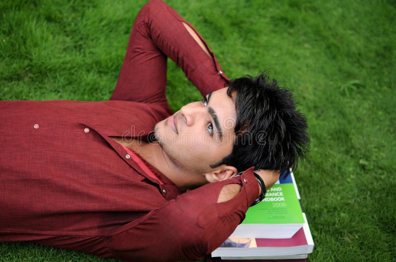 Young Indian teenager lying on grass. Young Indian boy lying on grass with books underneath. Making plans for future royalty free stock photo