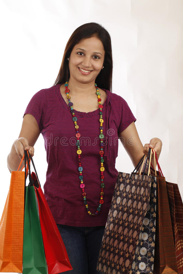 Young Indian teenager with shopping bags. Against white background royalty free stock photography