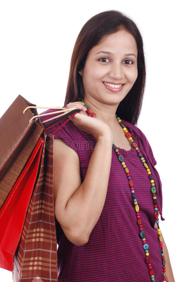 Young Indian teenager with shopping bags. Smiling young Indian female teenager with shopping bags against white background stock images