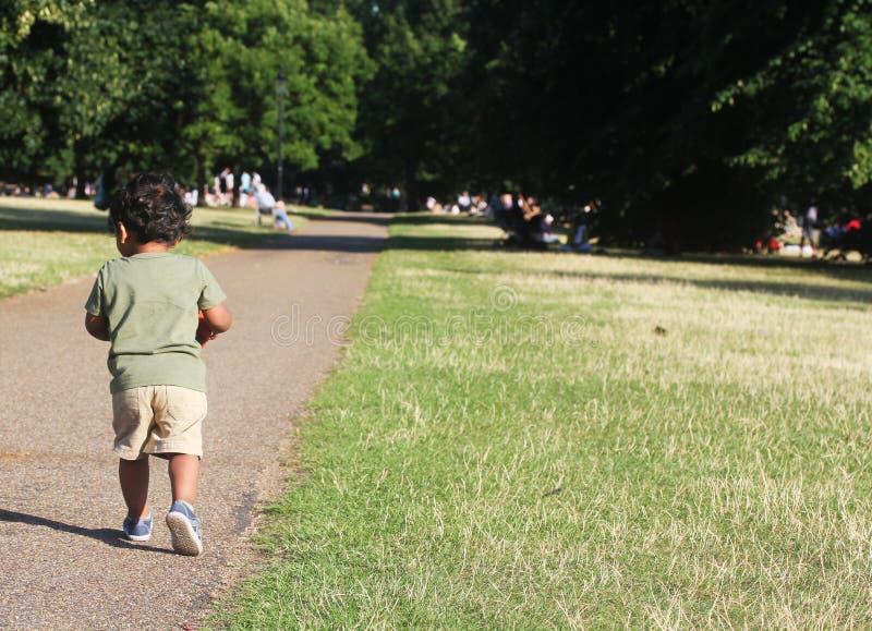 A Young Indian Toddler walking in garden. A Young Indian Toddler walking along a road along side green grass of a garden or a park stock photography