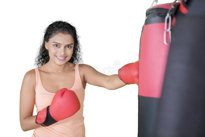 Young Indian woman exercising with a boxing bag royalty free stock photo