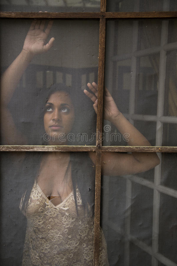 Young Indian Woman Gazing Out Old Screen Door Stock Photo -5309