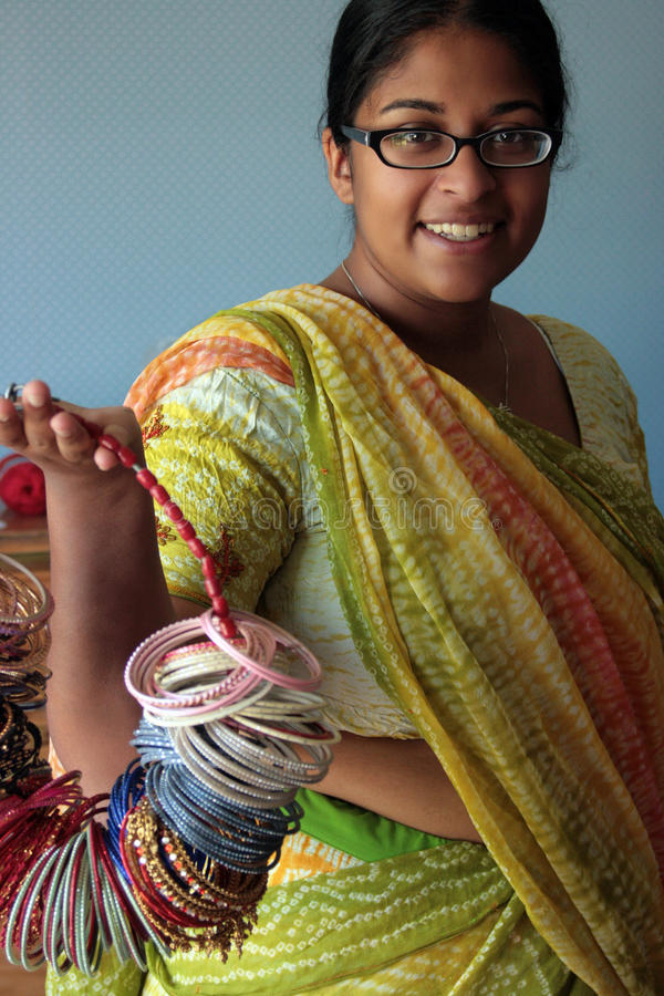 Young Indian Woman in a Sari with Bangles. A young Indian woman with glasses in a traditional sari holding a ring of bangle bracelets stock images