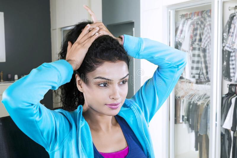 Young Indian woman tying her hair neatly at home stock photography