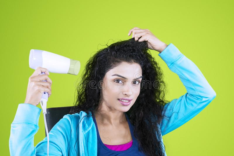 Young Indian woman using a hair dryer in the studio royalty free stock image