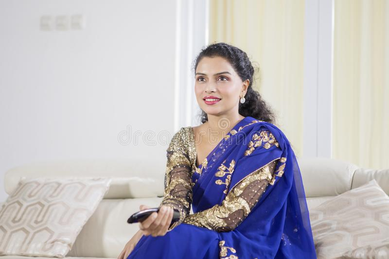 Young Indian woman watching TV at home stock photo