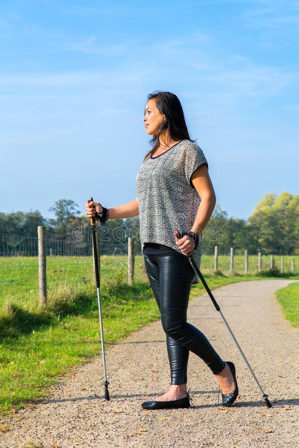 Young indonesian woman hikes with Nordic Walking sticks. Young indian indonesian woman hiking with Nordic Walking sticks in dutch nature stock photo