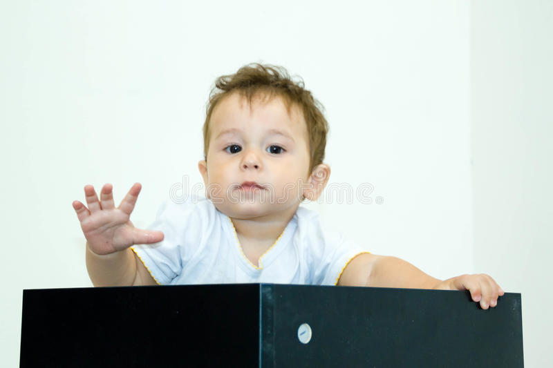 A young infant boy peeking out of a box on a white background. A young infant boy peeking out of box on a white background stock image