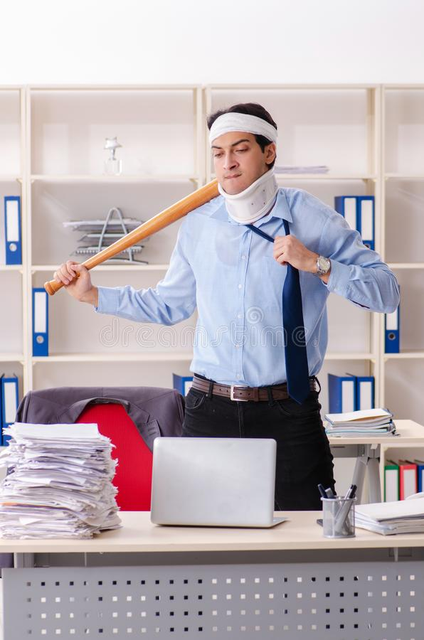 The young injured male employee working in the office royalty free stock photos