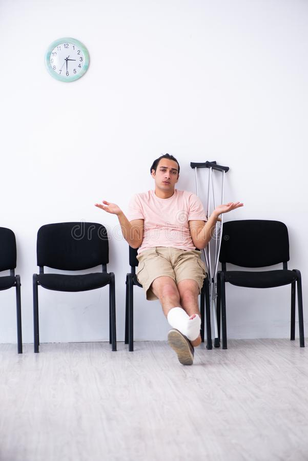 Young injured man waiting for his turn in hospital hall. The young injured man waiting for his turn in hospital hall royalty free stock photos