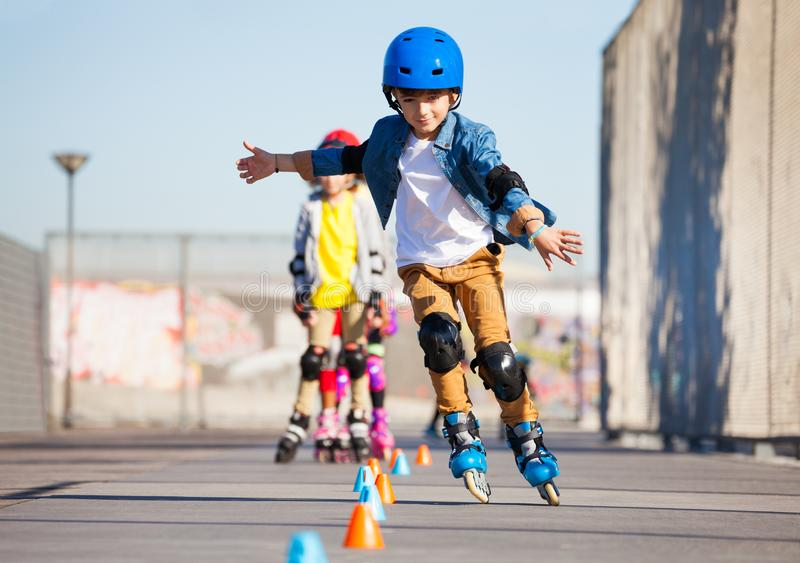 Young inline skater practicing forward slalom. Portrait of preteen boy, inline skater in protective gear, practicing forward slalom at outdoor skate park royalty free stock image