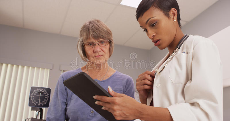 Young intelligent doctor looking at tablet with patient. An elderly patient consults with a young doctor stock images